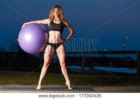 Portrait of a fitness woman with fit ball and having her workout break