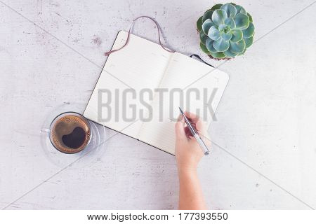 Open empty notebook on white wooden table with cup of coffee, succulent flower and someones hand with pen
