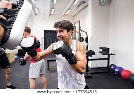 Handsome fit hispanic man in gym boxing with his unrecognizable personal trainer