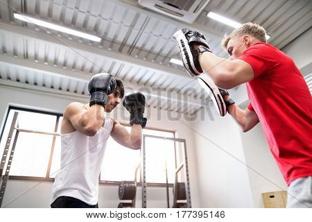 Handsome fit hispanic man in gym boxing with his personal trainer