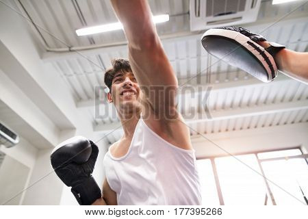 Handsome fit hispanic man in gym boxing with unrecognizable rival