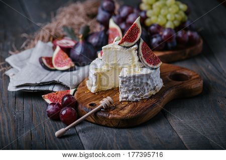 Homemade camembert cheese with fresh fruits on wooden board, dark background, selective focus, horizontal composition