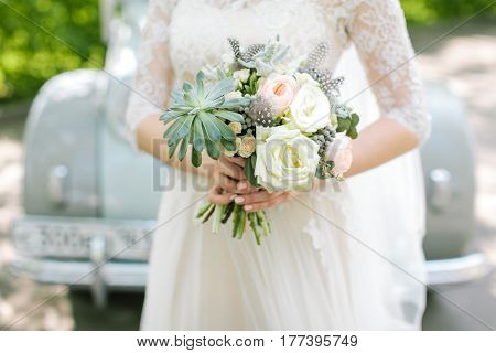 Beautiful woman in a white wedding dress holding a flowers bouquet from rose in hand on a retro car background outside. Wedding bridal bouquet.