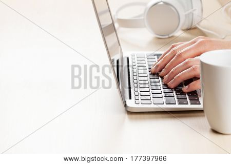 Woman working on laptop. Hands typing on keyboard on office desk. View with copy space