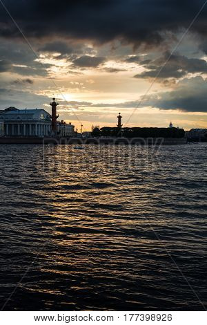 ST. PETERSBURG RUSSIA - JULY 13 2016: Old Saint Petersburg Stock Exchange and Rostral Columns at Neva river on sunset St. Petersburg Russia