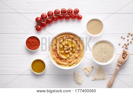 Homemade hummus traditional rustic healthy vegan dip chickpeas paste snack flat lay with natural ingridients, tahini, paprika, olive oil, pitta on table. Healthy vegetarian diet nutrition protein food