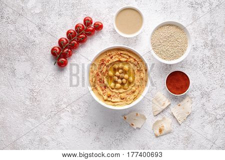 Hummus middle eastern homemade appetizer healthy vegan chickpeas paste dip snack flat lay with natural ingridients, tahini, paprika, olive oil, pitta. Healthy vegetarian diet nutrition protein food