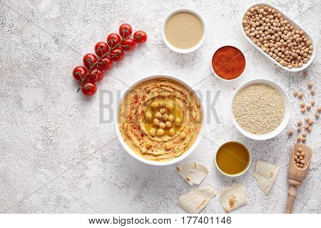 Plate of hummus flat lay with ingridients, healthy diet natural vegetarian snack protein food. Traditional mediterranean appetizer. Sesame, paprika, tahini, pita bread and olive oil on white table