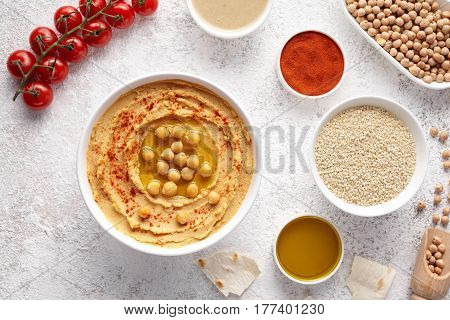 Chickpea hummus flat lay with ingridients, healthy diet natural vegetarian snack protein food. Traditional mediterranean appetizer. Sesame, paprika, tahini, pita bread and olive oil on white table