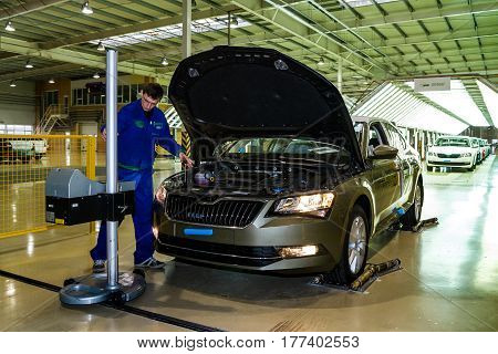 Solomonovo Ukraine - March 9 2017. The mechanic adjusts the headlights of the Octavia car in the workshop of the Transcarpathian plant of the Czech automaker from Skoda.