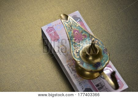 Top view of an Aladdin lamp placed over currency notes. Cash rewards - A conceptual image.
