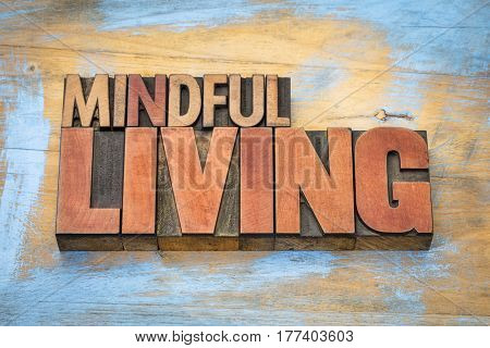 mindful living word abstract in letterpress wood type against grunge wooden background