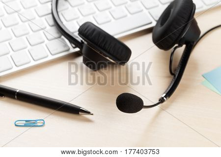 Office desk with headset laying on keyboard. Call center table