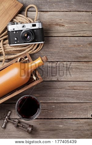 Red wine bottle and glass on wooden table. Top view with copy space