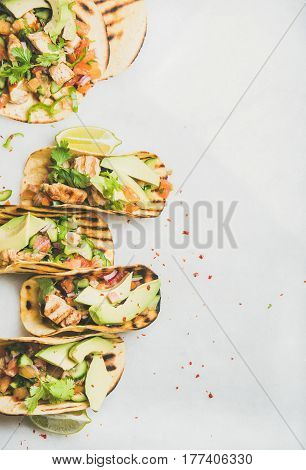 Healthy corn tortillas with grilled chicken fillet, avocado, fresh salsa, limes over light grey marble table background, top view, copy space. Gluten-free, allergy-friendly, weight loss concept