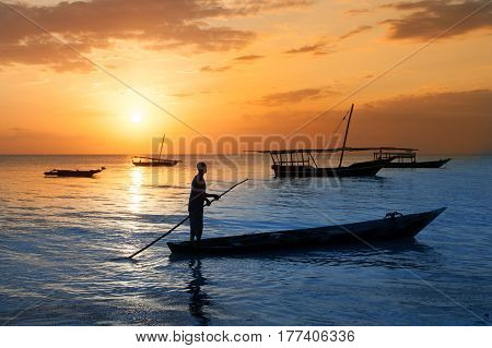 Man on a traditional boat off the coast of Zanzibar at sunset. Travel vacation adventure tourism concept.