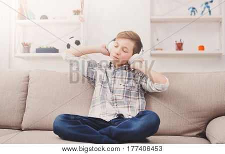 Teenager boy enjoy music - portrait of dreamy child in headphones on sofa indoors. Relax time, listen to music on couch at home