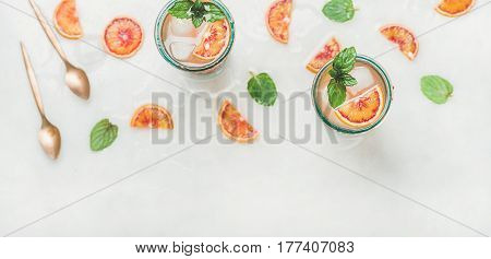 Blood orange fresh summer lemonade with ice and mint in glasses, light grey marble background, selective focus, top view, copy space