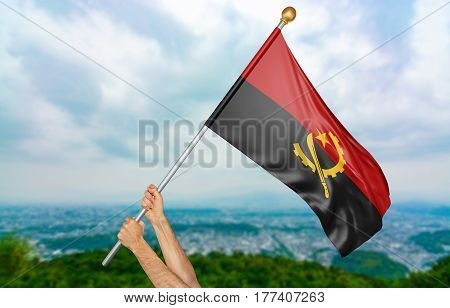 Young man's hands proudly waving the Angola national flag in the sky, part 3D rendering