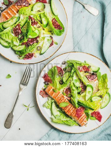 Healthy energy boosting spring salad with grilled salmon, blood orange, olives, cucumber and quinoa in white plates, top view, marble background. Clean eating, dieting, detox, weight loss concept
