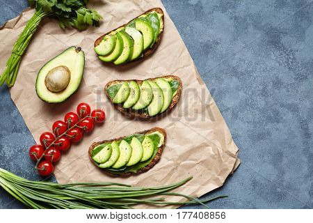 Sandwiches with avocado, guacamole and spinach on parchment on a concrete background. Useful breakfast, lunch. Low carb diet of organic products. Spring food mood. Flat lay food composition.