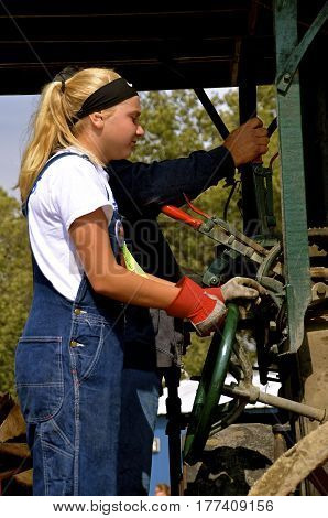 ROLLAG, MINNESOTA, Sept 2, 2016: An unidentified girl operates an old restored steam engine in a parade at the West Central Steam Threshers Reunion in Rollag, MN attended by 1000's held annually on Labor Day weekend.