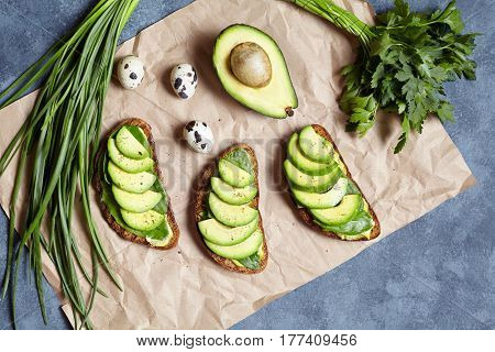 Avocado sandwiches with guacamole and spinach on parchment paper on a concrete background. Spring food. Low carb diet of organic products. Flat lay. Healthy breakfast or lunch concept.