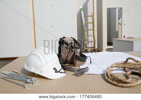 Building equipment hardware and building plan: helmet hammer rope screws worker's tool bag. Construction industry diy carpentry and hard at work concept.