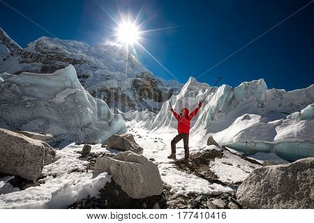 Trekkes Is Posing At Camera In Front Of Huge Glacier Falling From Everest Close To Everest Base Camp