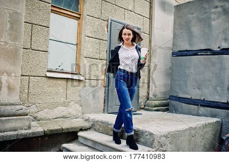 Portrait Of Stylish Young Girl Wear On Leather Jacket And Ripped Jeans With Cup Of Coffee. Street Fa