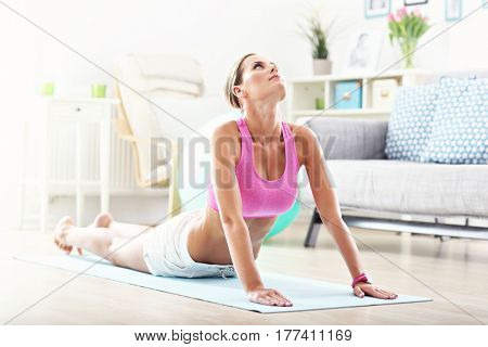 Young woman stretching at home in the morning