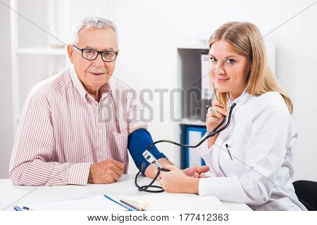 Doctor is measuring blood pressure to her patient.