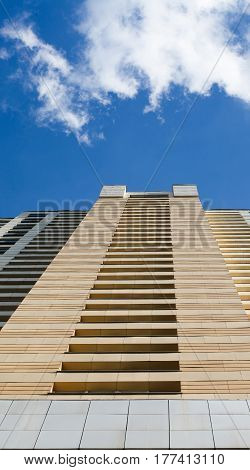 Urban landscape with skyscrapper on blue sky. Summer time cloudy weather background