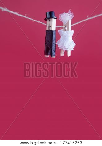 Bride and groom clothespin toys on clothesline. Abstract woman in white wedding dress and man with suit hat. Love concept photo. Macro view, shallow depth of field, copy space pink background. vertical