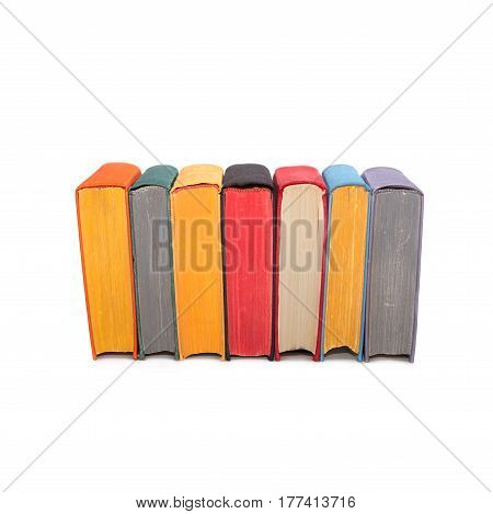 Stack of colorful books isolated on white background. Seven hardcover volumes. red black yellow pages
