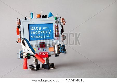 Data recovery concept. IT specialist robotic computer with red pliers, light bulb, warning message on blue display. Gray background, macro view photo.