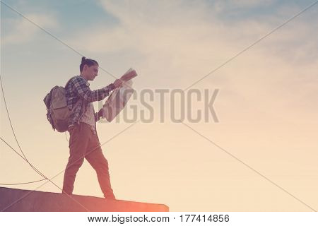 Brave and young traveler standing at sunset on high roof and looking at map