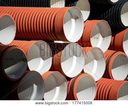 Pile of plastic water pipes, industrial background