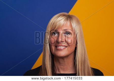 Mature blonde woman portrait on colorful background