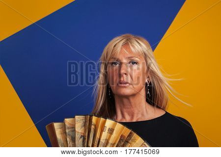 Middle-Aged Woman Having A Hotflash Holding a Fan