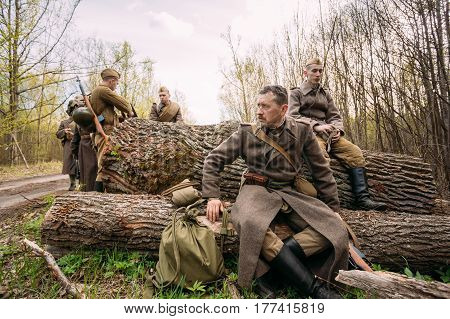 Pribor, Belarus - April 23, 2016: Group Of Re-enactors Dressed As Russian Soviet Infantry Red Army Soldiers Of World War Ii Stopped To Rest During A Campaign In Forest