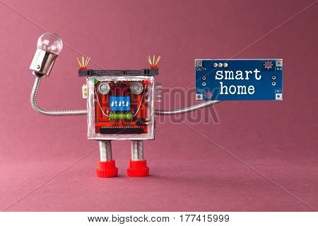 Smart home robotic automation concept. Colorful mechanical toy with light bulb lamp, blue circuit board and message. Violet background. macro view soft focus.