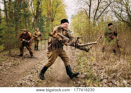 Pribor, Belarus - April 24, 2016: Group Of Unidentified Re-enactors Dressed As Soviet Russian Red Army Infantry Soldiers Of World War II removed from forest road lying tree for car movement At Spring
