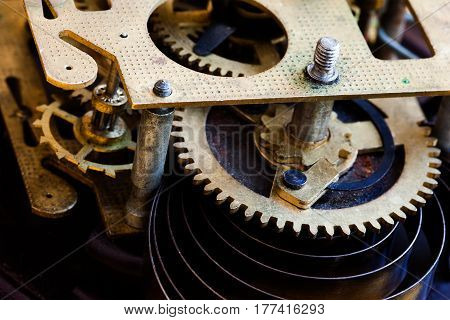 Antique mechanic clockwork mechanism, bronze cogs wheels macro view. Shallow depth of field, selective focus