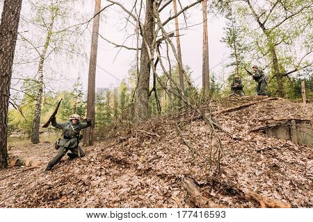Pribor, Belarus - April 24, 2016: Unidentified Re-enactor Dressed As German Wehrmacht Infantry Soldier In World War II Soldier Falls Down Dead On Battlefield At Historical Reconstruction In Autumn Forest