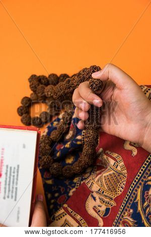 closeup picture of hand while doing Meditation with rudraksha mala or rosary beads