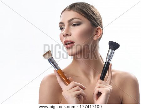Pure beauty. Beautiful sensual woman with perfect skin wearing professional makeup holding two makeup brushes near her face looking away copyspace beauty flawless confidence cosmetics concept