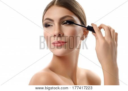 Mascara on Gorgeous young woman wearing professional makeup smiling applying mascara on her eye lashes using a brush isolated on white fashion style beauty cosmetic product advertising concept.