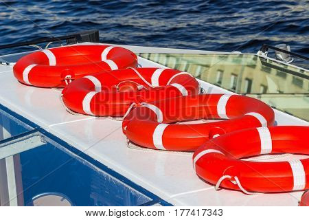 Many bright red lifebuoys on the boat.