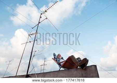 Young and happy man resting in the chair at the edge of the roof in the city
